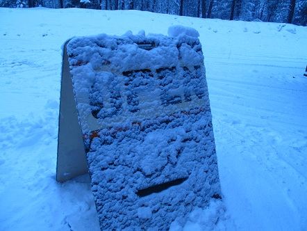 Open sign covered in snow